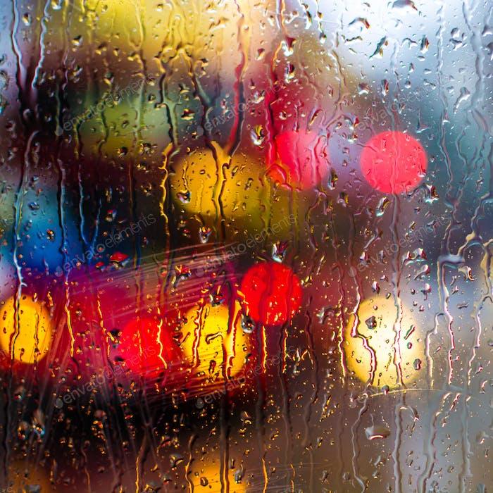 London bus seen through a glass window on a rainy day.