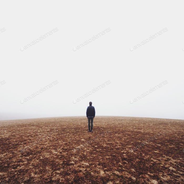 Hombre solitario de pie en tierra estéril