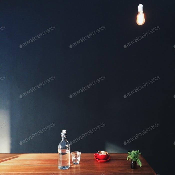 Flasche Wasser und Kaffeetasse auf dem Schreibtisch