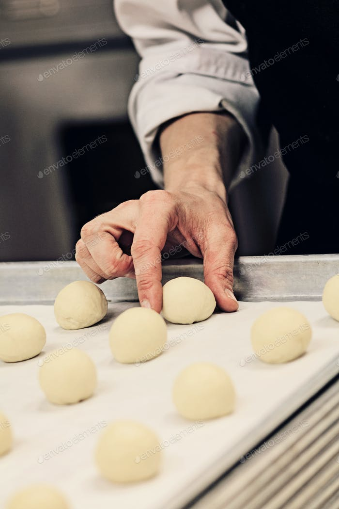 Close-up of hand of baker making dough