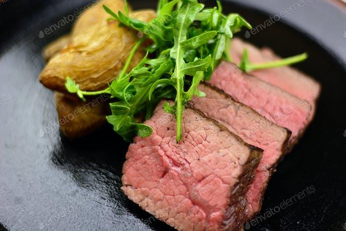 Rare steak, Yukon gold potatoes, & arugula