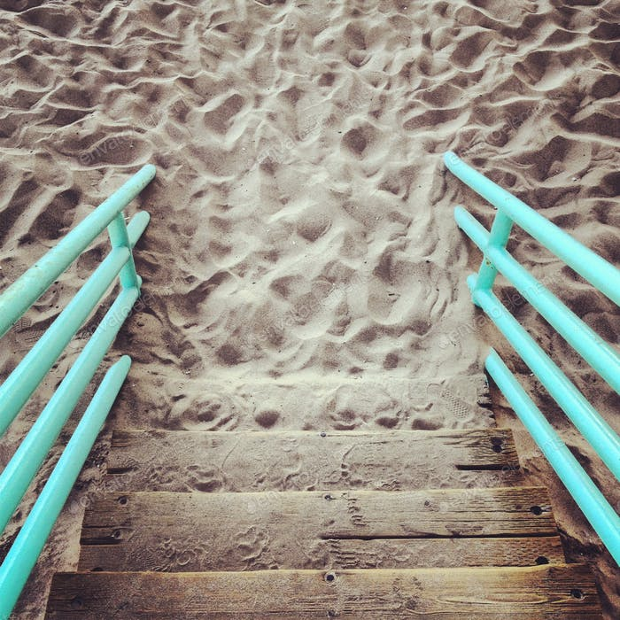 Wooden steps disappearing into sand