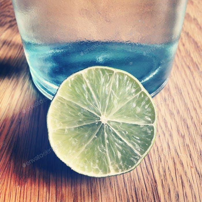Eine halbe Limette neben einem Trinkglas
