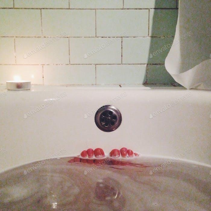 Human feet in bathtub