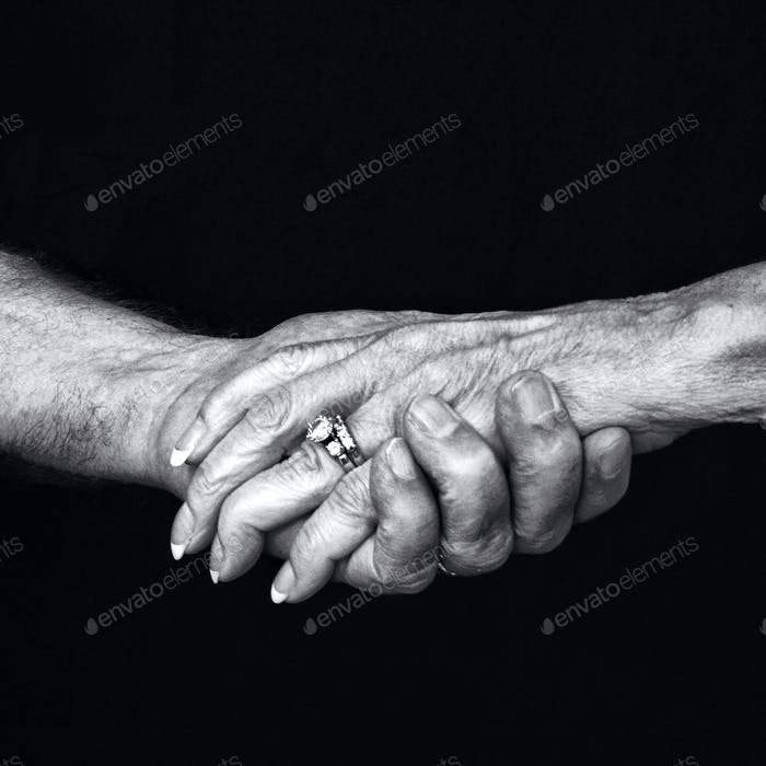 Old couple holding hands, close-up