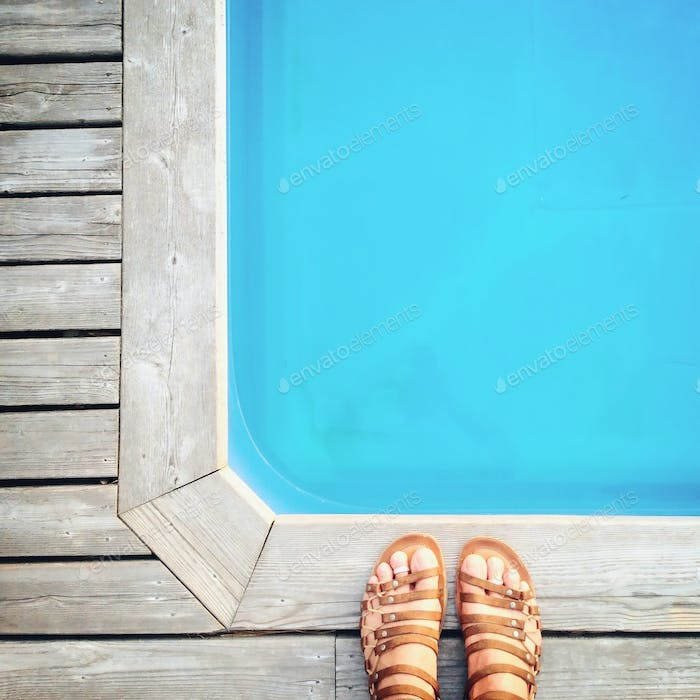 Summer. Sandals by the swimming pool.