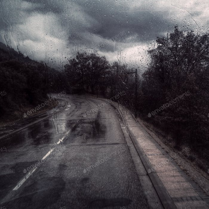 Road scene through windshield in rainy season