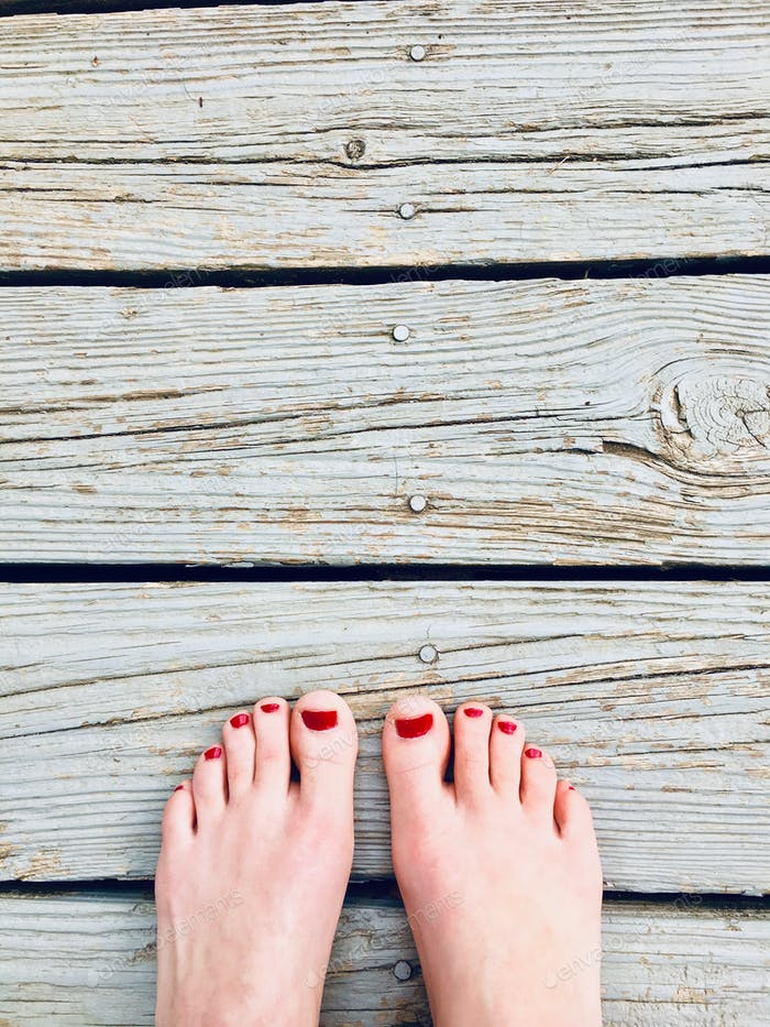 Two feet with painted toes against natural wood boards , symmetry