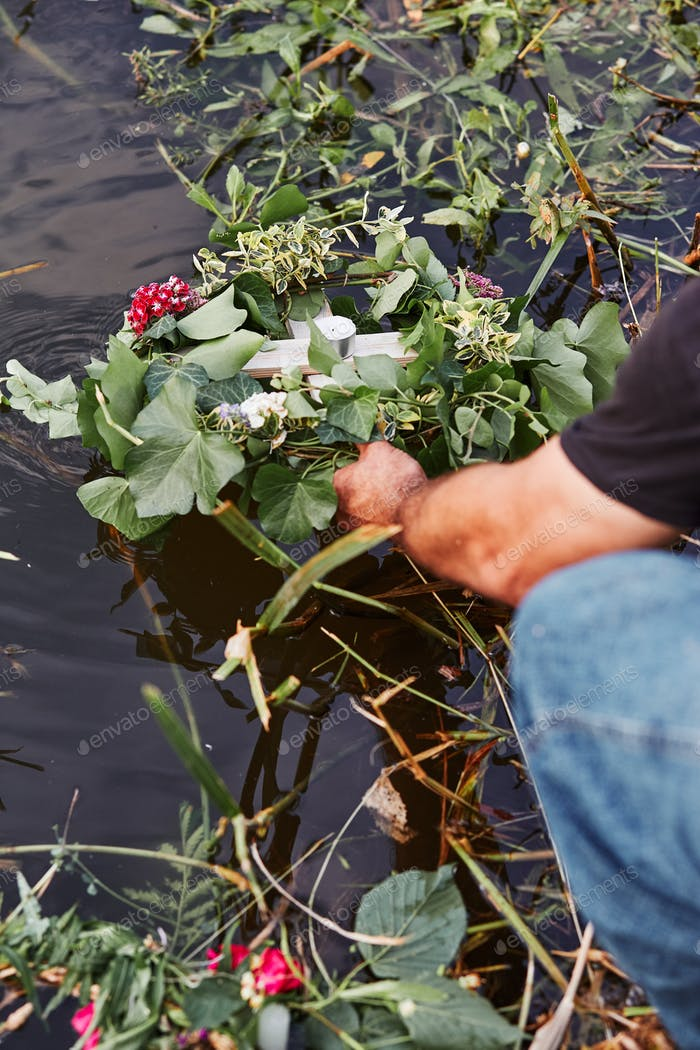 Wreaths of flowers and herbs. Man taking a wreath from a river. Midsummer divination