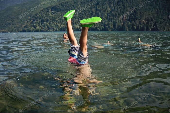 A young boy does a handstand in a lake.