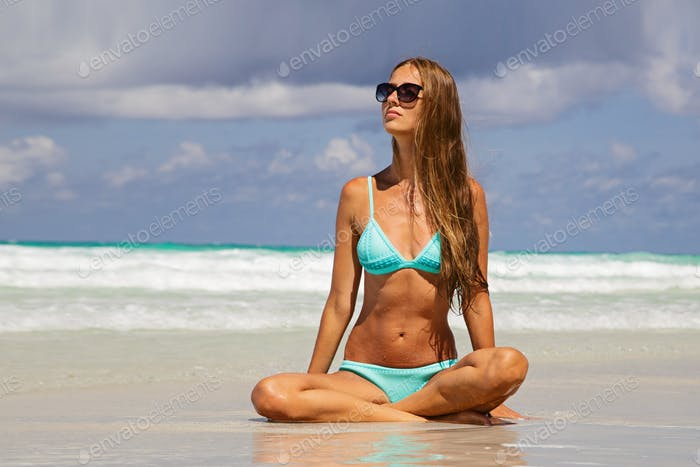 Slim young Caucasian woman 30 years old relaxing and sunbathing on beautiful beach at hot summer