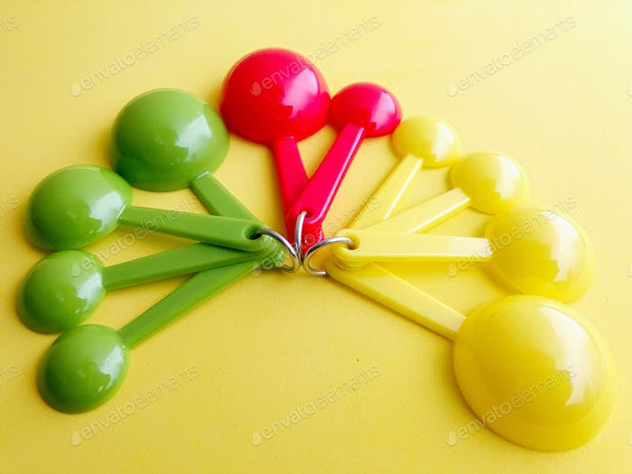 Colorful green, red, and yellow tablespoons and teaspoons on a yellow background