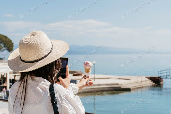 Rear view of young woman taking photos of ice cream on shore of sea in spring.