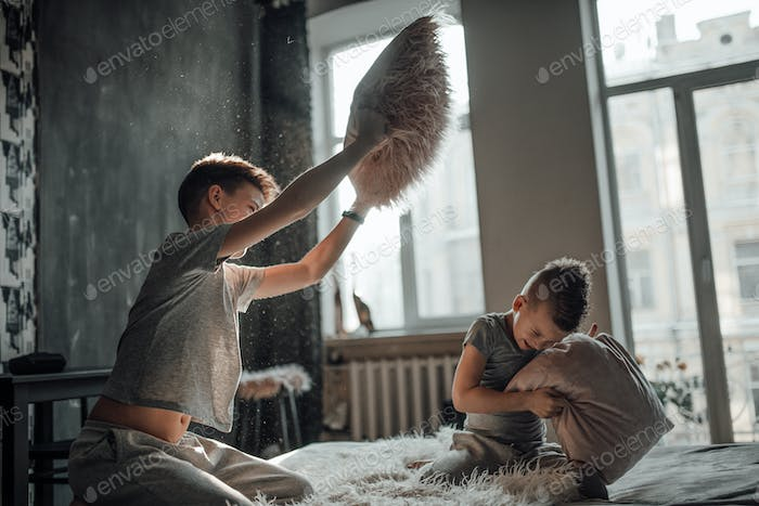 happy boys brothers playing banging pillow fight having fun together