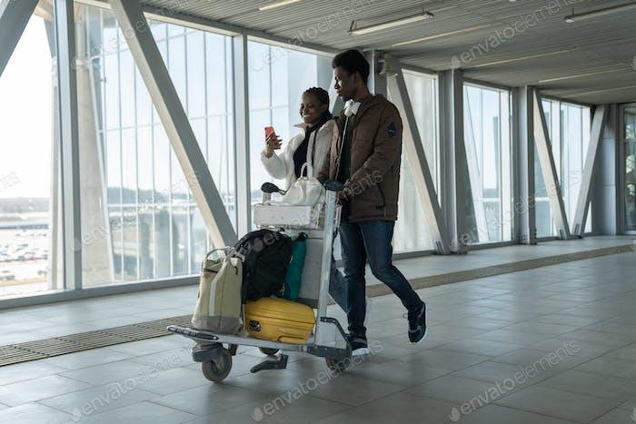 Glückliche afrikanische Paar-Reisende nach Ende der Corona-Pandemie. Schwarze Passagiere am Flughafen mit Gepäck