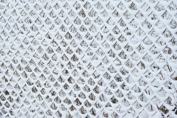 der Gitterzaun ist mit Schnee bedeckt