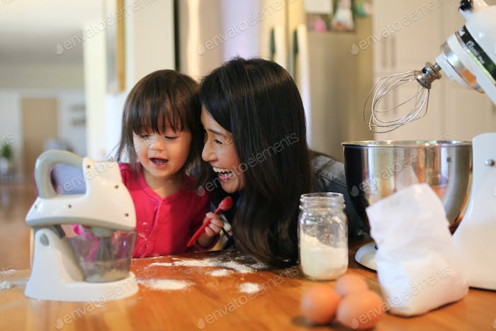 Mommy and daughter baking at home