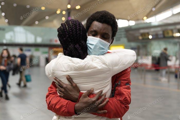 Afrikanisches Paar trägt Gesichtsmasken, die sich innerhalb der neuen Normalität am Flughafenterminal umarmen