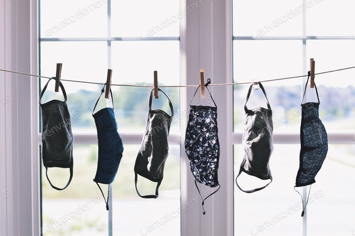 Handmade diy cotton cloth face masks hanging on a clothesline drying after being washed