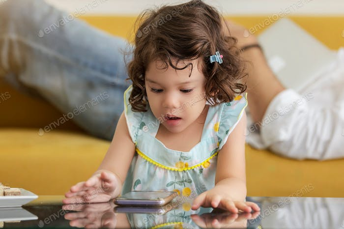 A kid using smartphone while father's naps on safa bed nearly her
