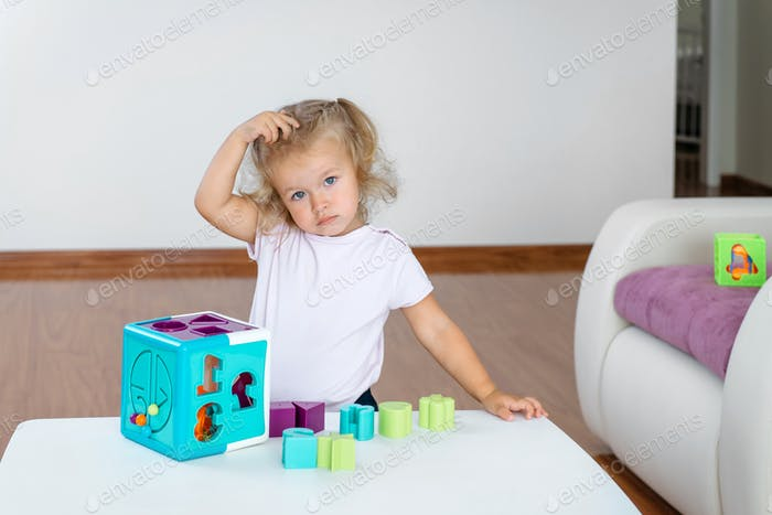 surprised small toddler girl with colorful blocks tower learning colors, letters and improve fine mo