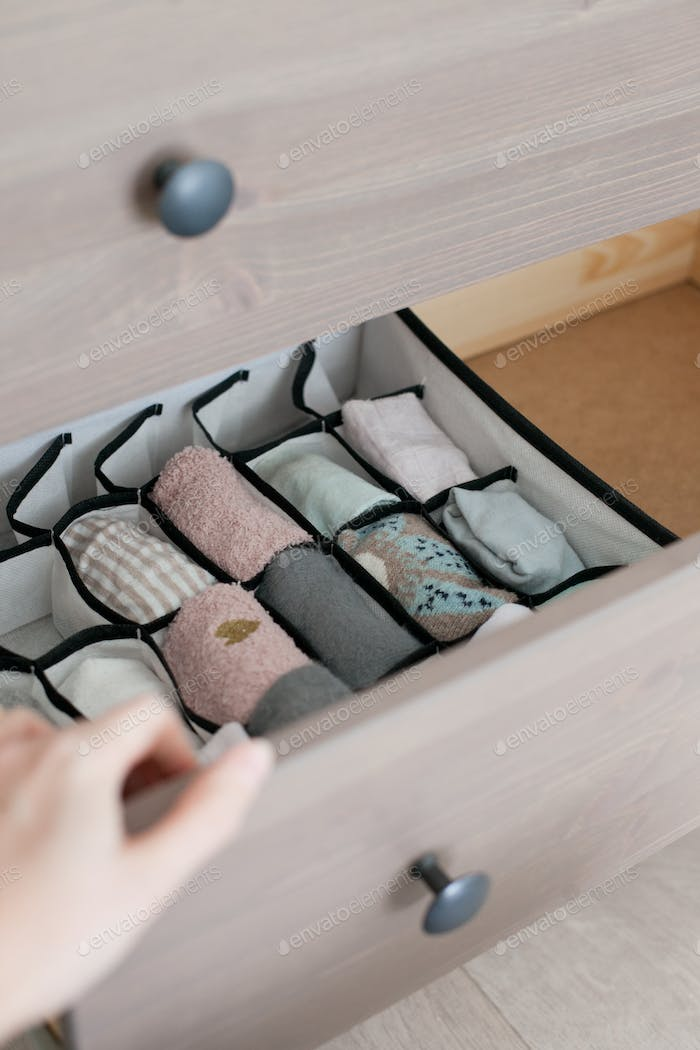 Organizing socks drawer and a gand opening the drawer (chest of drawers, folding socks