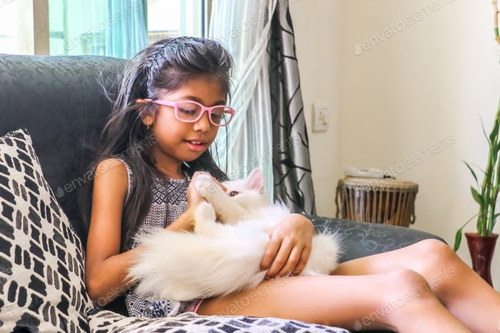 Girl child playing with her furry pet on the couch.