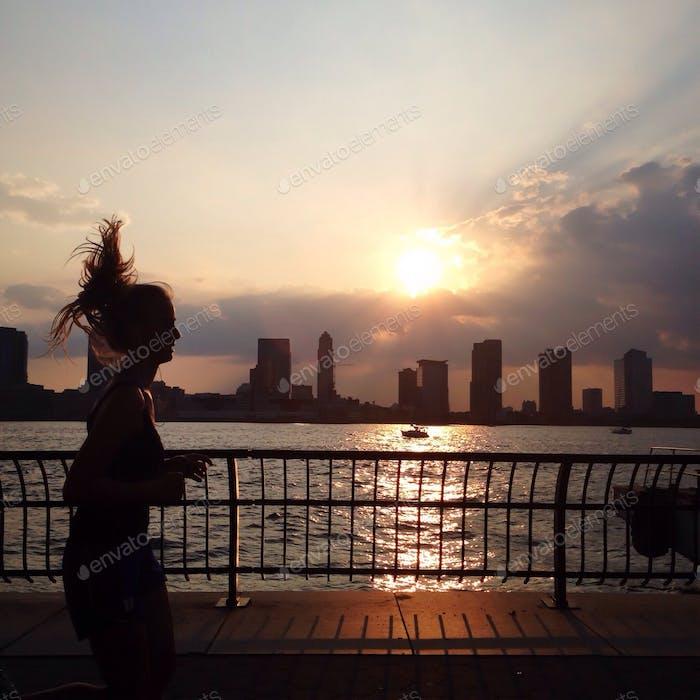 Frau joggt bei Sonnenuntergang am Fluss.