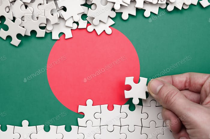 Bangladesh flag  is depicted on a table on which the human hand folds a puzzle of white color.