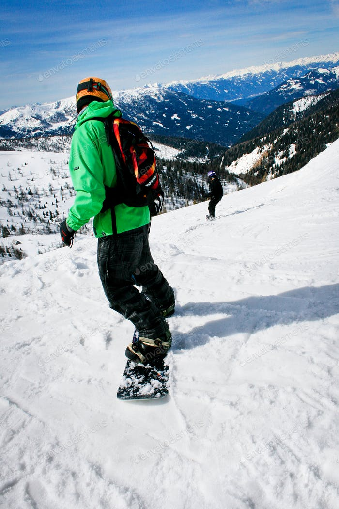 Couple snowboarding in winter mountains with horizon view.