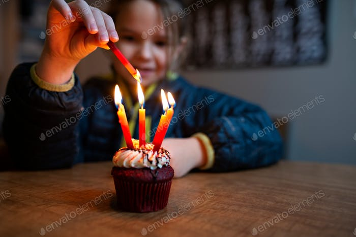 little girl lighting birthday candles on a birthday cake