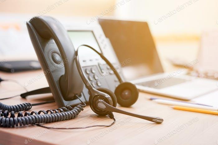 Nahaufnahme weicher Fokus auf Headset mit Telefongeräten am Schreibtisch für Kundendienst