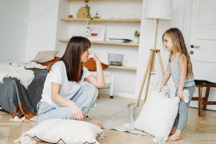 Young woman mother and little girl daughter playing having fun together at home