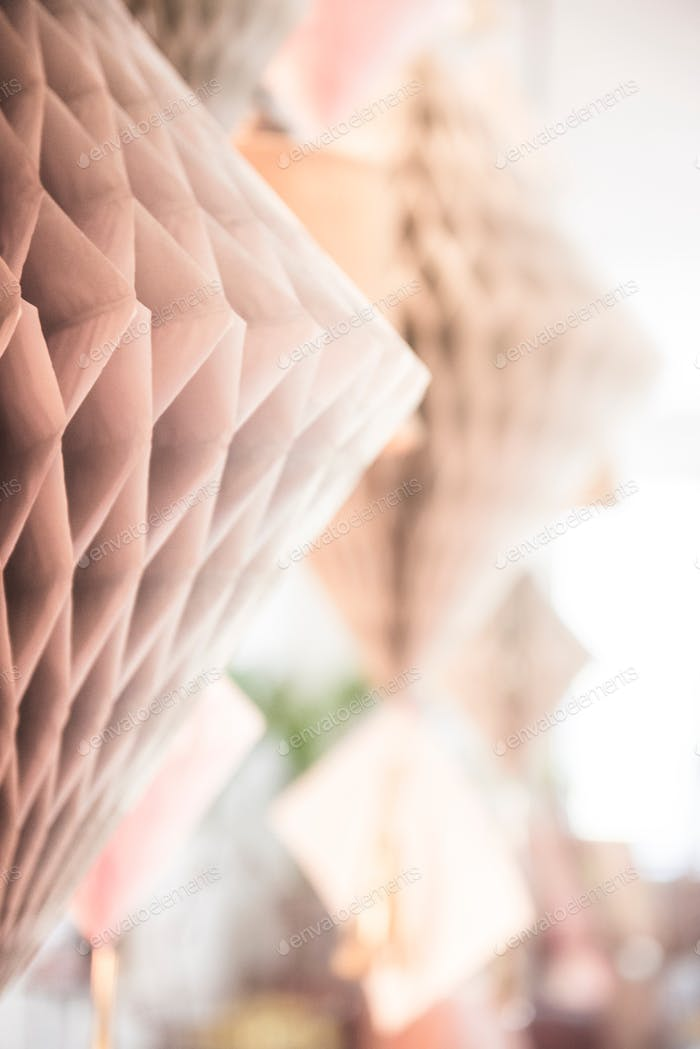 Bright and airy pale pink and peach honeycomb party decorations lit by sunlight with plenty of copy