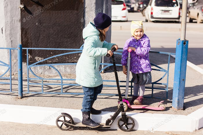 a girl in a hat and jacket rides a scooter