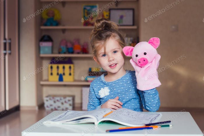 little girl doing homework at home with puppet pig