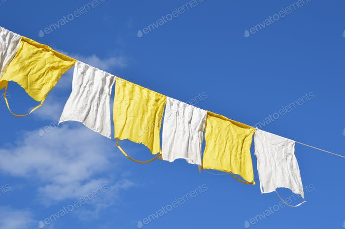 Colorful rags hanging on a rope against blue sky
