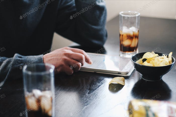 The young man drinks Coca-Cola with chips and uses a laptop
