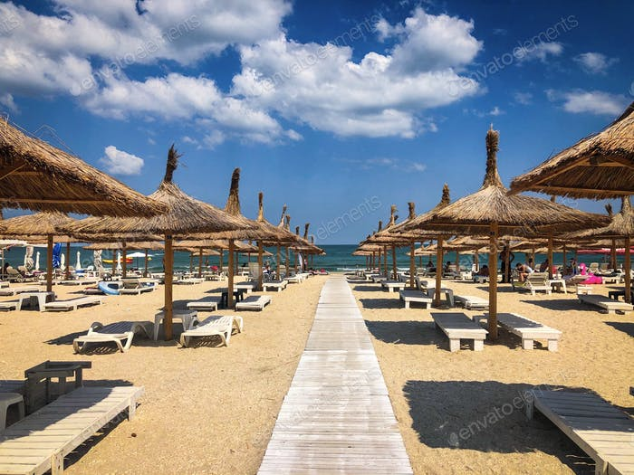 Empty beach with thatch umbrellas and wooden sunbeds on a day with blue sky and fluffy clouds