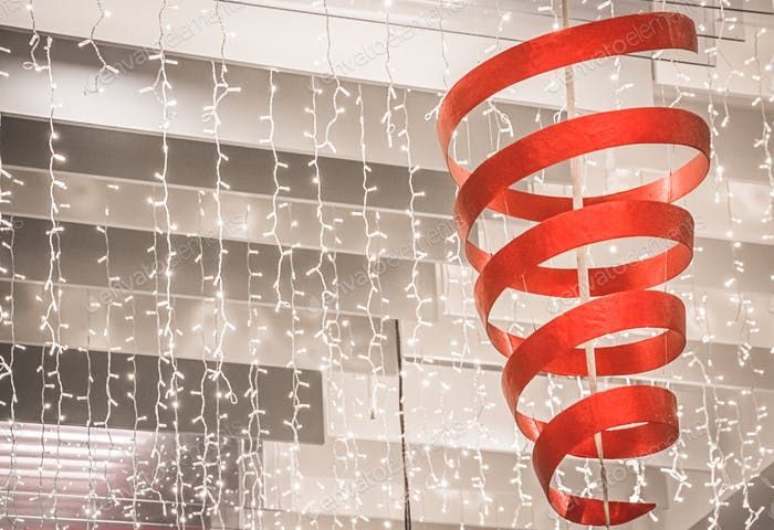 Verzierung mit rotem Band und vielen Lichtern zur Weihnachtszeit.