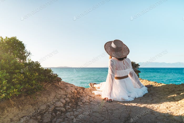 Boho tourist woman sitting on cliff over Mediterranean sea Canal D'Amour, chilling. Lady in dress