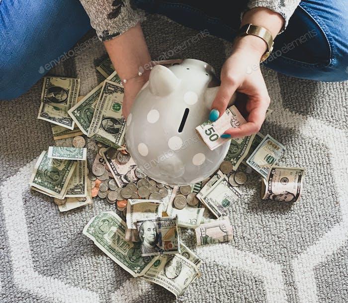 Einen 50-Dollar-Schein in ein Sparschwein stecken.