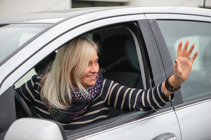 An smiling mature woman is driving a car ...NOMINATED!