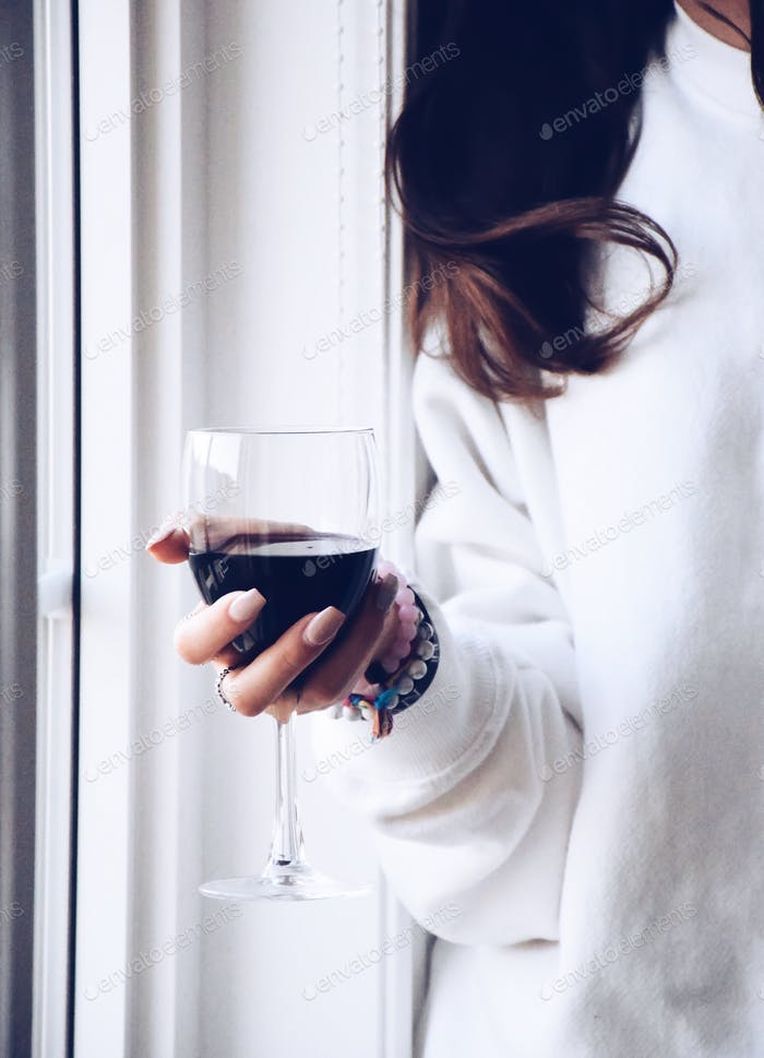 Young woman is holding a glass of wine standing by the window  💲