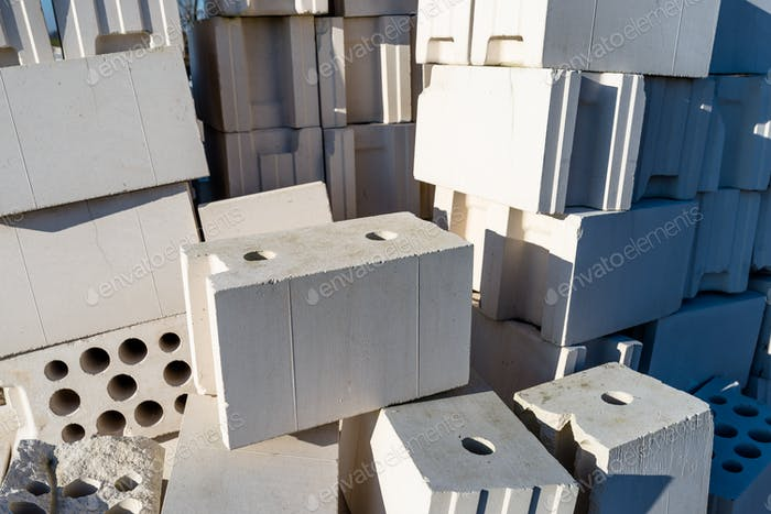 Heap of bricks from cellular concrete, white bricks, hollow bricks with hollow holes inside.