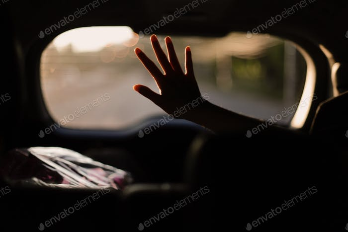 Rinding on car as a passenger, reach hand to enjoy sunset light during road trip to somewhere.