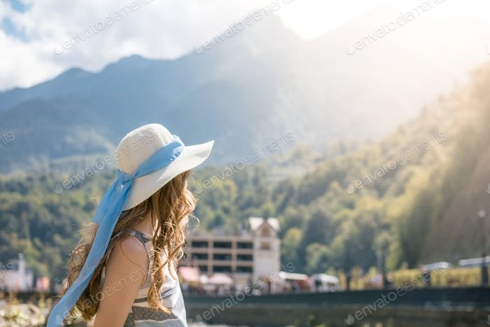 Young woman in a hat against a background of mountains. copy space. lifestyle. view from the back