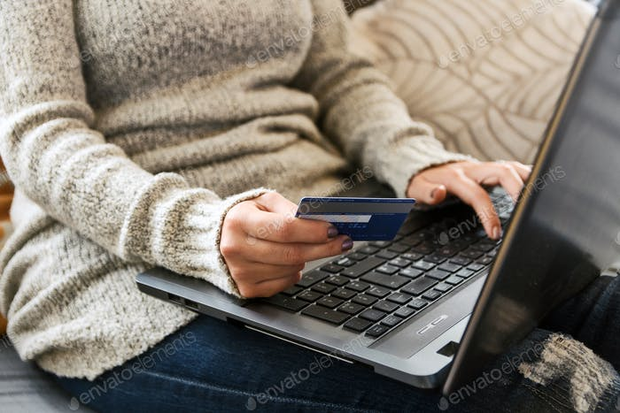Woman holding credit card, online shopping on laptop, unrecognizable person.