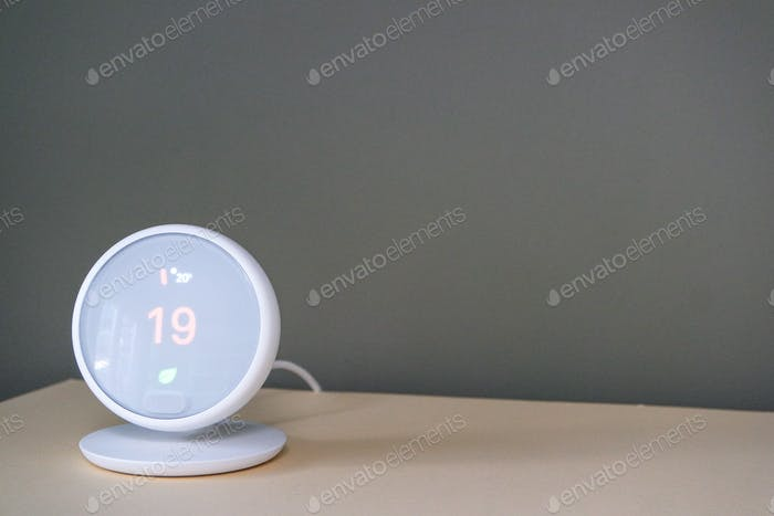 Modern smartphone or tablet operated thermostat. Temperature control, home comfort.