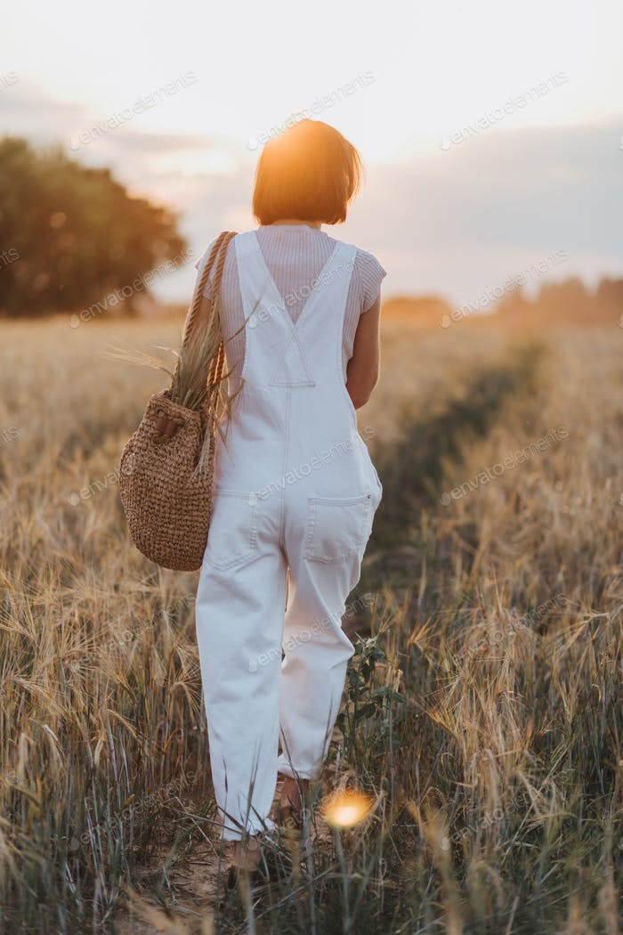 Young beautiful woman wearing white denim in nature. Warm weather, summertime, sunset, summer vibes.